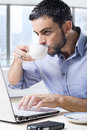 Young attractive businessman working on computer laptop drinking cup of coffee cup sitting at office desk in front skyscraper Royalty Free Stock Photos