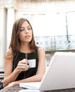 Young attractive businesswoman sitting luxurious coffee shop terrace her laptop holding cup coffee being thoughtful Royalty Free Stock Image