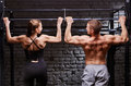 Young attractive caucasian crossfit man and woman working out in gym, rear view, couple Royalty Free Stock Photo
