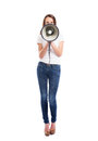 A young and attractive caucasian woman screaming on the megaphone in stylish jeans image is isolated white background Royalty Free Stock Photos