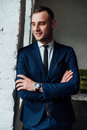 Young attractive and confident businessman in blue suit and black tie. Royalty Free Stock Photo