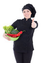 Young attractive cook woman in black uniform with vegetables thu Stock Photography