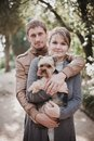 Young attractive couple going for a walk with their dog in park Stock Photo