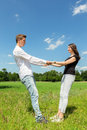 Young attractive couple holding each other in sunny meadow Royalty Free Stock Photo