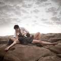 Young attractive couple sharing a moment outdoors on beach rocks with wine bottle Stock Photography