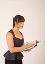 Young attractive female office worker taking notes Royalty Free Stock Images