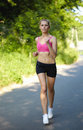 Young attractive female in pink run in park Royalty Free Stock Photos
