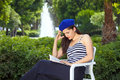 Young attractive female reading book romantic woman sitting on chair in park behind fountain Royalty Free Stock Photo