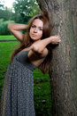 Young attractive female is standing near the tree Royalty Free Stock Image