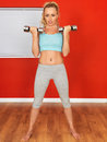 Young attractive fitness woman lifting weights with tied back blonde hair in her twenties to stay in shape and keep fit wearing a Stock Images