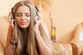 Young attractive girl enjoying music through headphones lying o Stock Photos