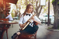Young attractive girl in white shirt with a saxophone sitting near caffe shop - outdoor in sity. Sexy young woman with sax looking Royalty Free Stock Photo