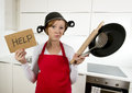 Young attractive home cook woman in red apron at  kitchen holding pan and household with pot on her head in stress Royalty Free Stock Photo