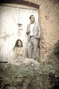 Young attractive indian couple standing together outdoors against old white doors in garden Royalty Free Stock Photos