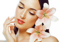 Young attractive lady close up with hands on face isolated flower lily brunette spa Royalty Free Stock Photo