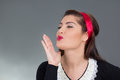 Young attractive maid sending air kiss over grey Royalty Free Stock Photo