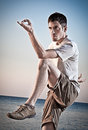 Young attractive man making thai chi movements on the beach of black sea Royalty Free Stock Image