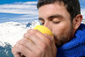 Young attractive man outdoors drinking cup of coffee or tea in cold winter warming his hands with the mug wearing blue scarf on Royalty Free Stock Photo