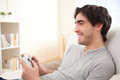 Young attractive man playing video games in a sofa Royalty Free Stock Photo