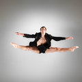 The young attractive modern ballet dancer jumping in black jacket over gray background Royalty Free Stock Photography