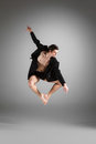 The young attractive modern ballet dancer jumping in black jacket over gray background Royalty Free Stock Images