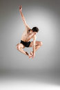 The young attractive modern ballet dancer jumping over gray background Stock Photos