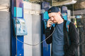 Young attractive modern man talking on the payphone Royalty Free Stock Photo