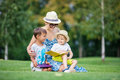 Young attractive mother reads a story book to her two small children while sitting on grass Royalty Free Stock Photo
