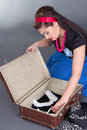 Young attractive pinup girl packing retro suitcase over grey Royalty Free Stock Images