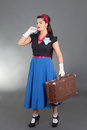 Young attractive pinup woman retro suitcase over grey Royalty Free Stock Photo