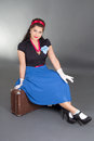 Young attractive pinup woman sitting retro suitcase over grey Royalty Free Stock Image