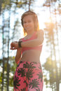 Young attractive runner listening to music wearing headphones and checking her smart watch. Sport, fitness, workout Royalty Free Stock Photo