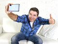 Young attractive s man taking selfie picture or self video with mobile phone at home sitting on couch smiling happy photo giving Royalty Free Stock Photos
