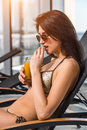Young attractive slim girl in bikini relaxing on deck chair in wellness spa hotel resort