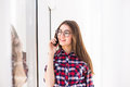 Young attractive smiling caucasian girl standing on background of window, talking per mobile phone. Royalty Free Stock Photo