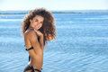 Young, attractive, smiling slender girl with curly hair in a black bathing suit on the beach Royalty Free Stock Photo