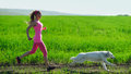 Young attractive sport girl running with dog in park Stock Photos