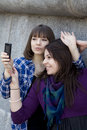 Young attractive teen girls take pictures by phone Royalty Free Stock Images