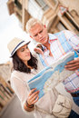 Young attractive tourist couple with city map in summer outdoor sightseeing Stock Photo
