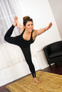 Young attractive woman balances standing pose yoga practice looks happy in Royalty Free Stock Image