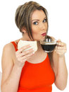 Young attractive woman with a black coffee and bacon sandwich dslr royalty free image holding glass cup of on white bread Royalty Free Stock Photography