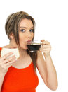 Young attractive woman with a black coffee and bacon sandwich dslr royalty free image straight highlighted hair pinned back Stock Images
