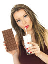 Young Attractive Woman Comparing a Chocolate Bar to a Glass of Sugar Royalty Free Stock Photo