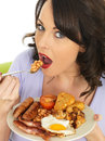 Young attractive woman eating a full english breakfast dslr royalty free image holding plate of two or sausages cooked tomato or Stock Images