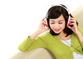 Young attractive woman enjoying music with headphone on the couch Royalty Free Stock Image