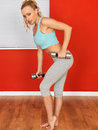 Young attractive woman exercising with weights blonde hair in her twenties wearing a crop top and grey jogging bottoms Stock Photo