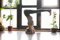 Young attractive woman in headstand pose, home interior backgrou Royalty Free Stock Photo