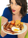 Young attractive woman holding a plate of full english breakfast dslr royalty free image two or sausages or two hash browns or Stock Photos