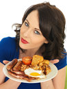 Young attractive woman holding a plate of full english breakfast dslr royalty free image two or sausages two or hash browns or Royalty Free Stock Photo