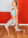 Young attractive woman lifting exercise weights with blonde hair in her twenties in a fitness workout exercising to stay healthy Stock Photography